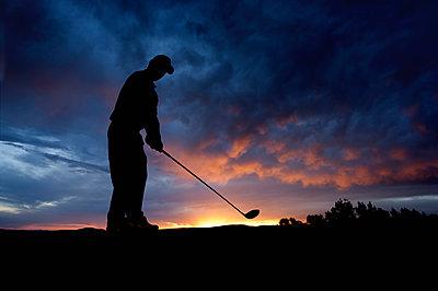 Caucasian golfer swinging golf club at sunset - p555m1478152 by Mike Kemp