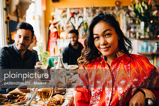 Portrait of smiling young woman sitting at table against multi-ethnic friends enjoying brunch in restaurant - p426m2046339 by Maskot