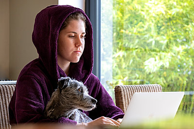 Young woman with dog works on laptop at home, stay at home due to Covid-19 - p1057m2185213 by Stephen Shepherd