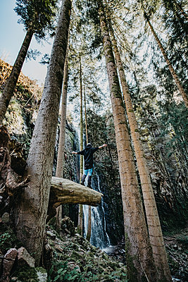 Man is standing on a tree stump - p1455m2092374 by Ingmar Wein