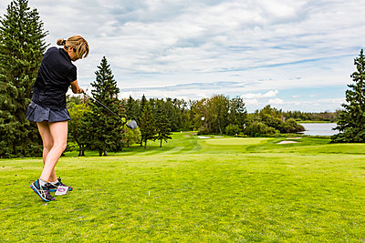 A female golfer skillfully driving a golf ball down the green grass of a golf course with the ball in mid-air; Edmonton, Alberta, Canada - p442m2019625 by LJM Photo