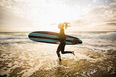 Caucasian surfer carrying board in waves - p555m1419624 by Mike Kemp