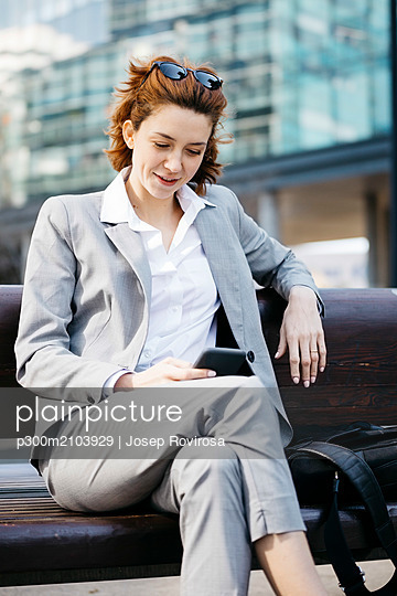 Young businesswoman sitting on a bench in the city, using smartphone - p300m2103929 by Josep Rovirosa