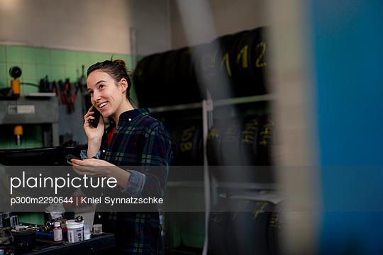 Female mechanic with digital tablet talking on smart phone at workshop - p300m2290644 by Kniel Synnatzschke