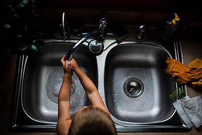 High angle view of boy washing hands in kitchen sink at home - p1166m1176228 by Cavan Images