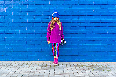 Girl wearing blue cap and oversized pink pullover standing in front of blue wall listening music with headphones - p300m2102753 von Eloisa Ramos