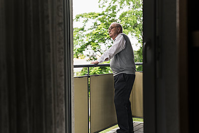 Senior man standing on balcony looking at distance - p300m2189523 by Uwe Umstätter