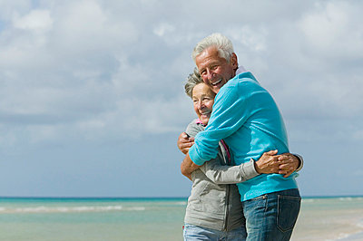 mature couple embracing on beach - p3163347f by Alessandro Ventura