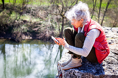 Woman sitting on rock texting on smartphone, Bruniquel, France - p429m1418327 by JAG IMAGES