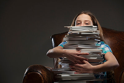 Girl holding pile of books - p429m803481f by Colin Hawkins