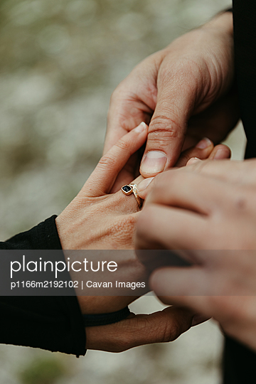 man puts custom engagement ring on her finger post proposal - p1166m2192102 by Cavan Images