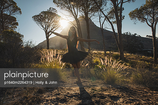 Woman in ballet skirt dances in the countryside - p1640m2264319 by Holly & John