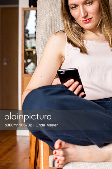 Woman sitting on chair at home looking at cell phone - p300m1166792 by Linda Meyer