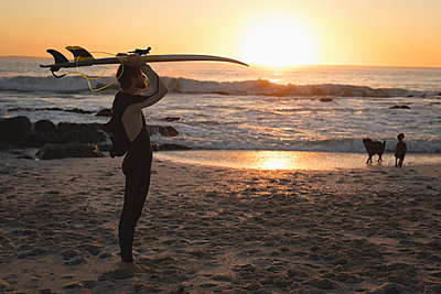 Surfer carrying surfboard on head during dusk - p1315m1565381 by Wavebreak