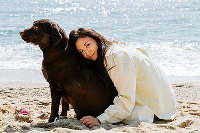 Beautiful woman embracing dog on sand during sunny day - p300m2281352 by VITTA GALLERY