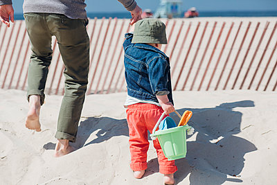 Father holding hands of boy carrying toy bucket while walking at beach - p300m2287160 by Ashley Corbin-Teich