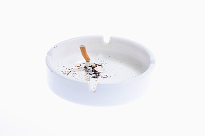 A cigarette butt put out in a white ashtray - p301m730752f by Larry Washburn