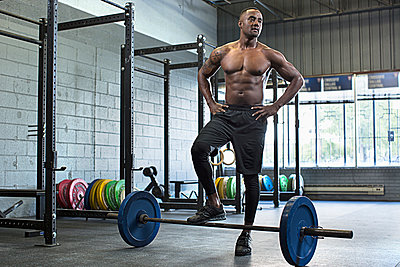 Black athlete standing at barbell in gym - p555m1304734 by DreamPictures
