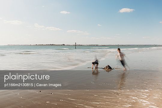 Two children running on beach against blue sky - p1166m2130815 by Cavan Images