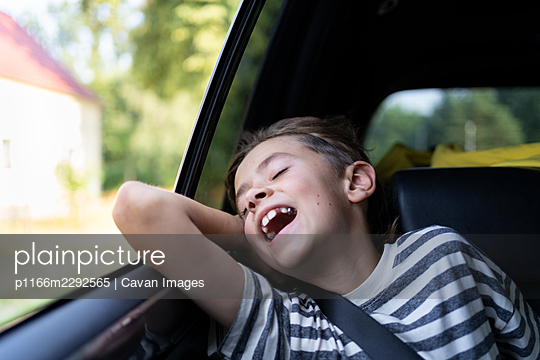 A young boy is  enjoys the warm wind from an open car windowdow - p1166m2292565 by Cavan Images