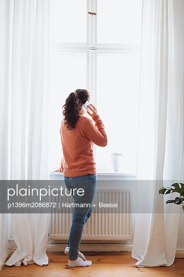 Junge Frau steht am Fenster und telefoniert - p1396m2086872 von Hartmann + Beese