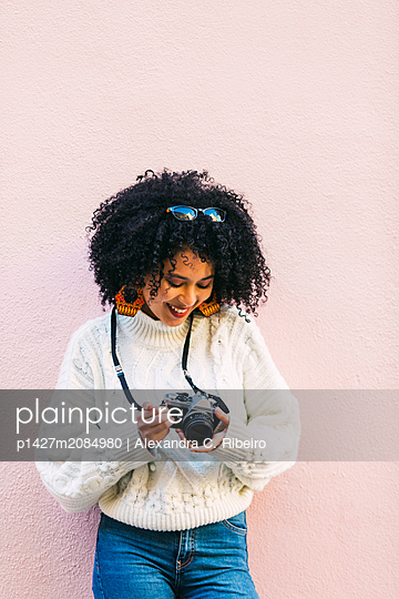 Young woman holding camera against pink wall - p1427m2084980 by Alexandra C. Ribeiro
