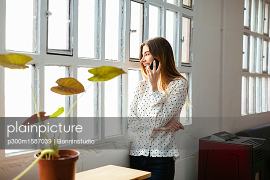 Happy young woman on cell phone at the window in office - p300m1587039 von Bonninstudio