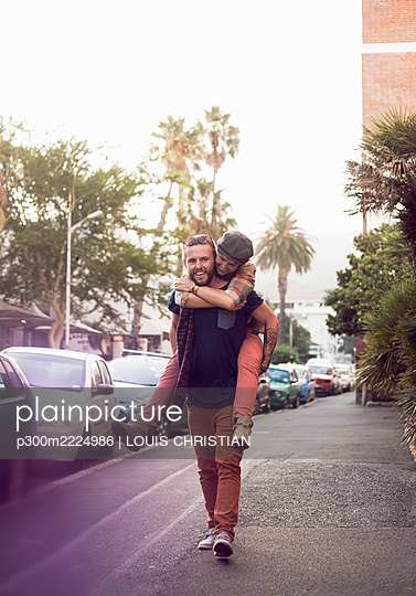 Mid adult man taking piggyback for woman on street in city - p300m2224986 by LOUIS CHRISTIAN