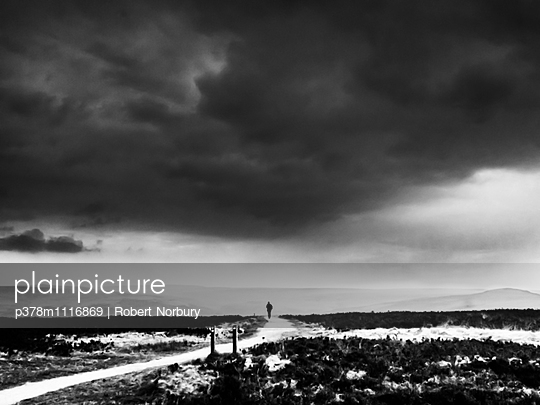 Distant silhouette of a man on moorland path during a stormy sky. Yorkshire, England, United Kingdom - p378m1116869 by Robert Norbury