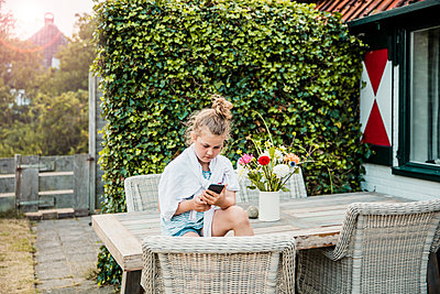 Girl sitting on terrace table using cell phone - p300m1499575 by Robijn Page