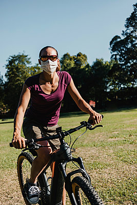 Woman in face mask riding electric mountain bike at park - p300m2240162 by David Molina Grande