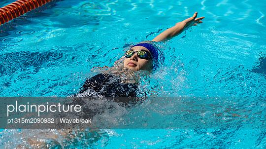 Female swimmer swimming backstroke in swimming pool - p1315m2090982 by Wavebreak