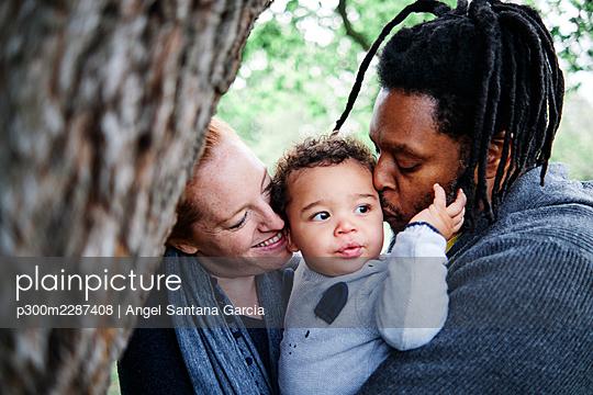 Happy family kissing cute son at park - p300m2287408 by Angel Santana Garcia