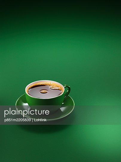 Cup of coffee or espresso against green background - p851m2205839 by Lohfink
