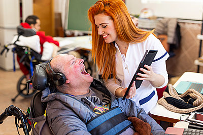 Smiling nurse showing digital tablet to happy disabled man in nursing home - p300m2243790 by DREAMSTOCK1982