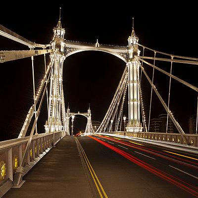 Urban bridge lit up at night - p429m756370 by Alex Holland