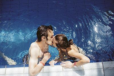 Caucasian couple kissing in swimming pool - p555m1491643 by Aliaksandr Liulkovich