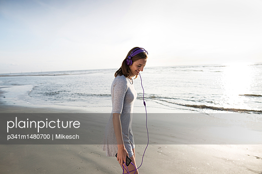 Young woman on beach with headphones - p341m1480700 by Mikesch