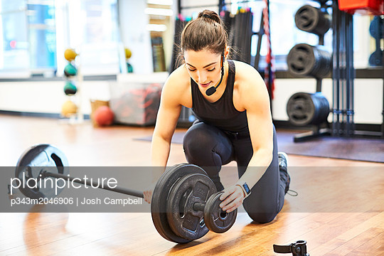 Fitness instructor putting weights on barbell in gym - p343m2046906 by Josh Campbell