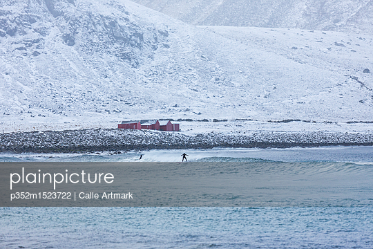 People surfing in the sea below snowy hills in Norway - p352m1523722 by Calle Artmark