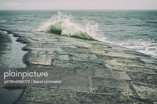 Wave on harbour wall - p378m2096772 by David Lichtneker
