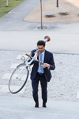 Businessman carrying bicycle on staircase - p1026m1139958 by Patrick Frost