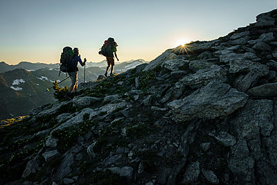 Silhouette of two hikers at sunset with mountains in background, BC - p1166m2113335 by Cavan Images