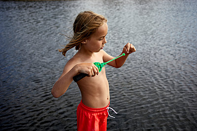 Boy on the waterfront holding a small fishing rod - p1511m2223094 by artwall