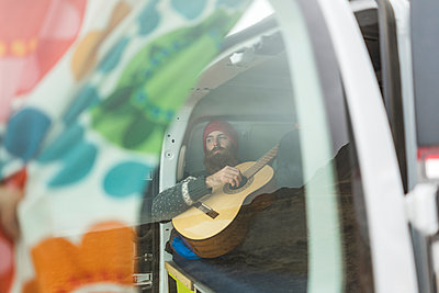 Man lying in van playing guitar - p300m1587989 von VITTA GALLERY