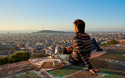 Man lying on boyfriend's lap at observation point against clear sky during sunrise, Bunkers del Carmel, Barcelona, Spain - p300m2257347 by Veam