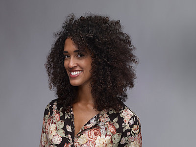 Portrait of smiling young woman with nose ring and Afro in front of grey background - p300m973539 by Rainer Holz