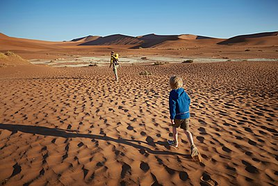Boy walking in desert, Namib Naukluft National Park, Namib Desert, Sossusvlei, Dead Vlei, Africa - p429m1029874 by Stephen Lux