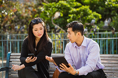 Chinese business people using technology on city bench - p555m1219415 by Erik Isakson