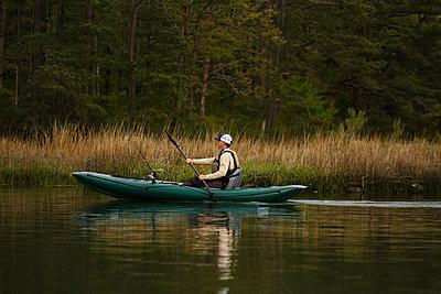 Caucasian man fishing on kayak - p555m1503978 by Roberto Westbrook